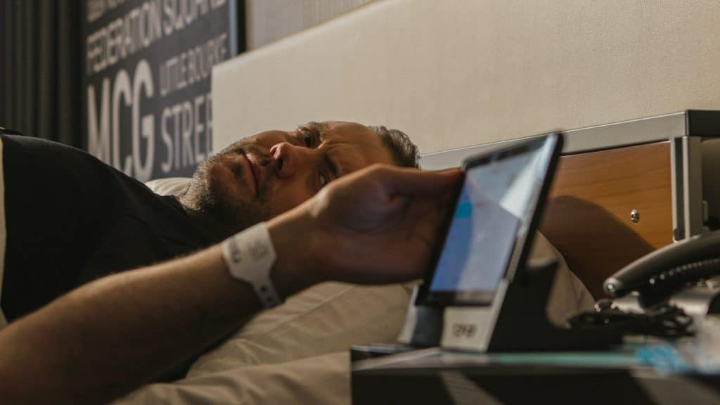 Corporate video production Melbourne, man in hospital reaching tablet.